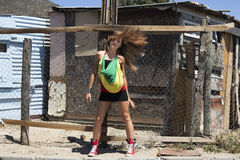 Headbanging is actually cool. Caucasian female having fun tossing her hair about while standing in the street of an African township Stock Photo