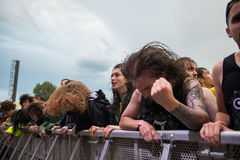 Headbanging crowd in the first row at a hardcore concert. BONTIDA, ROMANIA - JULY  15, 2017: Crowd of hardcore fans headbanging during an Architects concert at Royalty Free Stock Photo