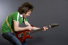 Headbanging guitarist playing an electric guitar. Over black background Royalty Free Stock Image