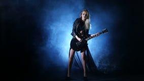Headbanging sexy woman plays guitar at the concert stock footage