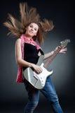 Headbanging woman guitarist playing her guitar. Over dark background Stock Image