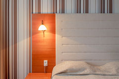 Headboard and bed in a clean hotel room. Hotel room bed and headboards, lamp and night stand, striped wallpaper and lighting Stock Images