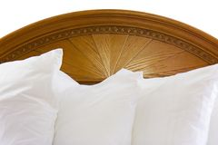 Headboard and pillows. Wooden headboard isolated with white fluffy pillows royalty free stock photo