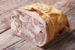 Headcheese closeup on table tied with twine and wrapped in paper Stock Photography