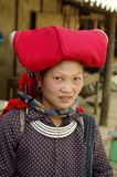 Headdress of a Hmong woman red Sapa. Woman of the ethnic (minority) Hmong red pompoms. This beautiful woman wears the headdress of married women. A basket in the Stock Image