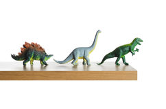 Headed for extinction. Dinosaurs figurines placed together on a ledge Royalty Free Stock Image