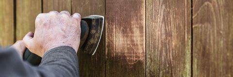 Header, Carpenter is sanding weathered wooden boards with a elec. Tric sander, copyspace Stock Images