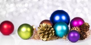 Header with christmas theme, colorful baubles and fir cones. Shiny background Royalty Free Stock Image