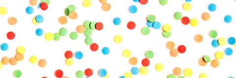 Header, colorful sugar confetti or sprinkles on white background. Concept party and celebrate stock photography