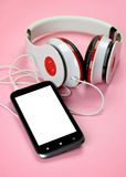 Headfones and smartphone on pink background. Royalty Free Stock Photos