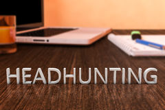 Headhunting. Letters on wooden desk with laptop computer and a notebook. 3d render illustration Stock Images