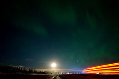 Heading for the Dalton Highway. An green aurora is backlit by the moon while a truck's headlights light up the forest and it's taillights mark it's passage Royalty Free Stock Photos