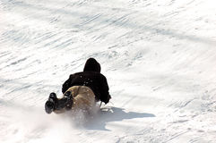 Heading down fast. A young man going fast on his sledge Stock Images