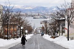 Heading down the Hakodate slope in winter. A lady walking down the slope in Hakodate, Hokkaido, Japan. with a view of the port bay stock photography