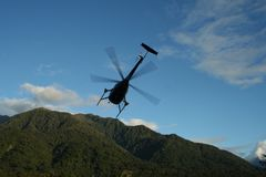 Heading for the hills. Helicopter takes off to the hills, Westland, New Zealand Stock Photography