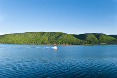 Heading Home. Cape Breton Boat Motoring through Calm Channel with Tree Clad Hills in Background Royalty Free Stock Image