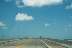 Heading to Key West. Well know seven mile bridge of the Florida Keys heading to Key West. Electrical poles, sky,clouds aand sea are part of the scene Stock Photography