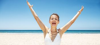 Happy woman in swimsuit at sandy beach on sunny day rejoicing Royalty Free Stock Photo