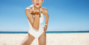 Smiling woman in white swimsuit blowing air kiss at sandy beach Stock Images
