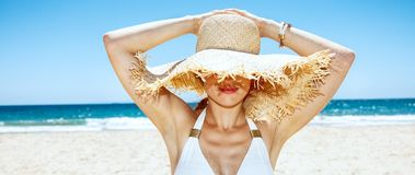 Smiling woman in swimsuit hiding under big straw hat at beach. Heading to white sand blue sea paradise. Smiling woman in white swimsuit hiding under big straw Royalty Free Stock Photography