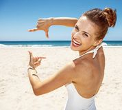 Smiling woman in swimsuit at sandy beach framing with hands. Heading to white sand blue sea paradise. Smiling woman in white swimsuit at sandy beach on a sunny Royalty Free Stock Image
