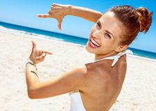 Smiling woman in swimsuit at sandy beach framing with hands. Heading to white sand blue sea paradise. Smiling woman in white swimsuit at sandy beach on a sunny Royalty Free Stock Photography