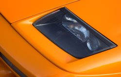 Headlamp orange Italian super car. Headlamp on a vivid orange Italian super car Royalty Free Stock Photo