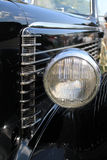 Headlamp and side hood detail. Headlamp between hood and fender. side hood details such as vents. 1937 lasalle series 50 convertible coupe at car event in south stock images