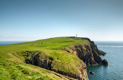 Headland on the Mull of Galloway. View of a headland with a lighthouse jutting into the sea on the Mull of Galloway, South West Scotland on a summer day Stock Images