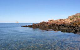 Headland with pink granite and blue sea Stock Photography