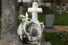 Headless angel. Destroyed tombstone at the abandoned cemetery. Stock Photos