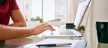 Headless crop of a caucasian male using his laptop Royalty Free Stock Photography