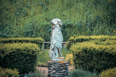 Headless statue of with a sheep in the garden Stock Image