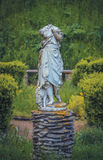 Headless statue of with a sheep in the garden Stock Photo