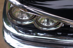Headlight on antique car. Close up of front grill and headlight on antique black car royalty free stock photo