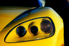Headlight Assembly. Car - close view of triple light headlight assembly - bright yellow car Royalty Free Stock Photo