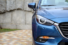 Headlight of Blue Vehicle on Car Park Near Stone Wall. Blue vehicle on the paving blocks near stone wall at the private parking royalty free stock photo