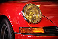 Headlight of classic sports car. Close up of red classic sports car headlight Royalty Free Stock Photos