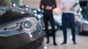 Headlight of the electric car. Shooting in front of the car. Close-up: The camera focuses on the headlight of the electric car. At the background in blurred stock video