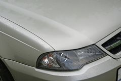The headlight and the hood of the car. Raindrops on the wing of the car. Royalty Free Stock Photo