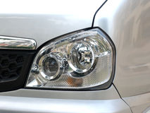 The headlight of a microbus. The headlight of a grey silver microbus royalty free stock photography