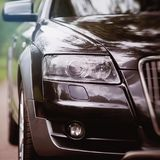 Headlight of a modern car. The front wheels of the car. Modern Car exterior details. Headlight of a modern grey sport car. The front lights of the car. Modern Stock Image