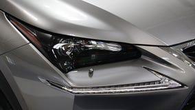 Headlight of modern luxurious japanese hybrid engine limousine. Displayed on car expo stock images
