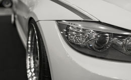 Headlight of a modern sport car.The front lights of the car and alloy wheel. Modern Car exterior details Stock Images