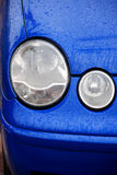 Headlight on navy blue car Stock Images