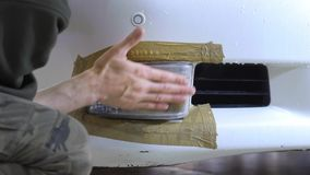 Headlight Polishing, processing of car lights. A car service worker polishes the headlight of a passenger car stock video footage