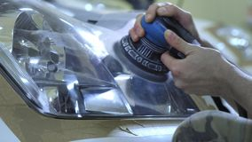 Headlight Polishing, processing of car lights. A car service worker polishes the headlight of a passenger car with a stock video footage
