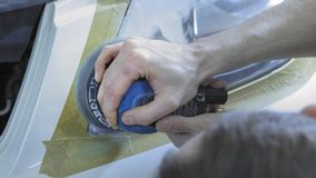 Headlight Polishing, processing of car lights. A car service worker polishes the headlight of a passenger car with a stock video