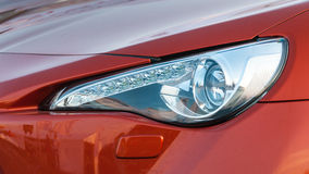 Headlight of red car close up Stock Photos