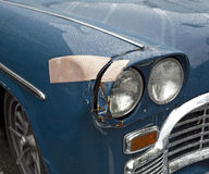 Headlight Repair. Ouch. Large bandage on classic car`s fender and headlight. Fun. Horizontal stock photos